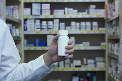 Pharmacist holding white vitamin bottle in front of dispensary shelves Stock Photography