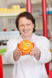 Pharmacist Holding Yellow Piggybank In Pharmacy Royalty Free Stock Photography