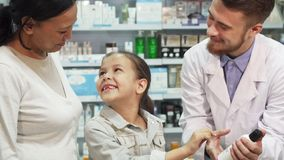 Friendly pharmacist shows little girl one of the tubes stock photography