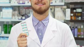 The pharmacist holds pills in his hands and shows a thumbs up. The pharmacist holds a packet of pills in his hand. With his other hand he shows a thumbs up. He stock video