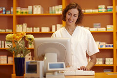 Pharmacist in the internet. Pharmacist typing on computer behind pharmacy counter Royalty Free Stock Image