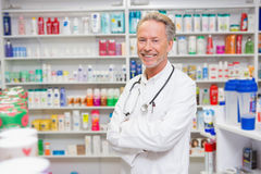 Pharmacist in lab coat with stethoscope and arms crossed. In the pharmacy Stock Photography