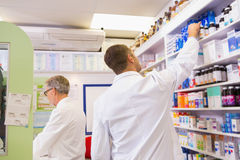 Pharmacist in lab coat taking jar from shelf Royalty Free Stock Photo