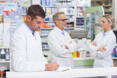 Pharmacist in lab coat writing a prescription Stock Photography