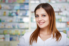 Pharmacist lady closeup. Closeup of a woman pharmacist over blurred background of medicine shelves Royalty Free Stock Images