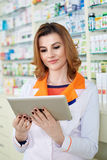 Pharmacist lady looking on a tablet Royalty Free Stock Photos