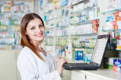 Pharmacist lady using laptop. Female pharmacist checking medicine stock availability on her laptop Royalty Free Stock Photo
