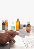 Pharmacist and laptop computer. Pharmacist holding prescription with laptop computer with pills in background royalty free stock photo