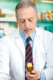 Pharmacist looking at a bottle stock image