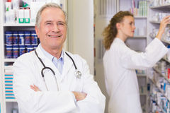 Pharmacist looking at camera with student behind him Stock Photography
