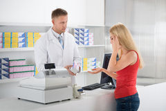 Pharmacist Looking At Customer Suffering From Headache Royalty Free Stock Image