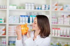 Pharmacist Looking At Piggybank In Pharmacy Royalty Free Stock Photos