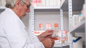 Pharmacist looking at pills in a shelf with a clipboard Royalty Free Stock Images