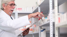 Pharmacist looking at pills in a shelf Stock Photo