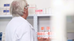 Pharmacist looking at pills in a shelf Stock Image