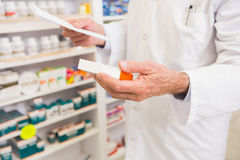 Pharmacist looking at prescription and medicine Stock Images