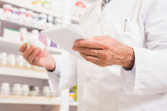 Pharmacist looking at prescription and medicine Stock Photo