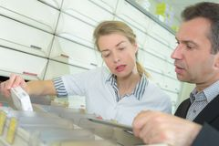 Pharmacist looking at prescription and medicine in pharmacy Royalty Free Stock Photography