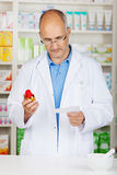 Pharmacist looking seriously at prescription Royalty Free Stock Photography