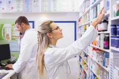 Pharmacist looking up at medicines Royalty Free Stock Photo