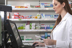 Pharmacist looks for medicine. Female pharmacist searches medicine holding a prescription in her hand Stock Photos