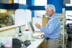Pharmacist making prescription record through computer Stock Photography