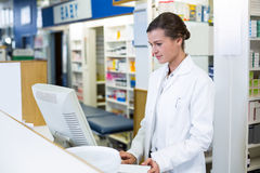 Pharmacist making prescription record through computer Royalty Free Stock Photography