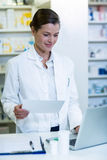 Pharmacist making prescription record in laptop Stock Images