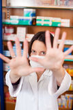 Pharmacist In Mask Gesturing Stop Sign At Pharmacy Stock Photography
