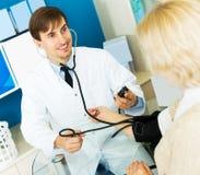 Pharmacist measures pressure at elderly woman Stock Photo