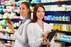 Pharmacist med assistenten i apotek Royaltyfria Foton