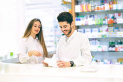 Pharmacist packing drugs at the pharmacy. Female pharmacist helping him Royalty Free Stock Photo
