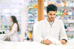 Pharmacist packing drugs at the pharmacy stock image