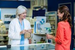 Pharmacist packing medicine in paper bag for customer Stock Photo
