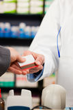 Pharmacist with paying customer in pharmacy Royalty Free Stock Photo