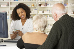 Pharmacist in pharmacy with senior couple Royalty Free Stock Image
