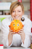 Pharmacist with piggy bank in the pharmacy Stock Photo