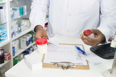 Pharmacist With Pill Bottles And Clipboard At Counter Royalty Free Stock Photo