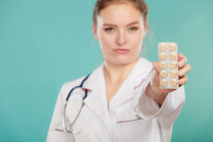 Pharmacist with pills medication. Ways of treatment. Pharmacist doctor in white medical unform apron showing pills. Woman specialist with stethoscope holding Stock Images