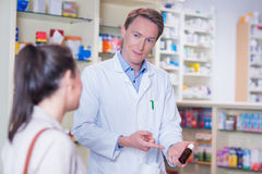 Pharmacist pointing a flask of pills in front of a customer Royalty Free Stock Photography