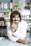 The pharmacist. Portrait of a smiling pharmacist with friendly look leaning on a desk and with one hand on the chin stock images