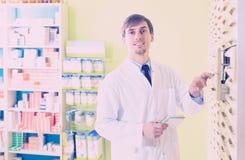 Pharmacist posing in pharmacy depot. Smiling adult male pharmacist posing in pharmacy depot Stock Images