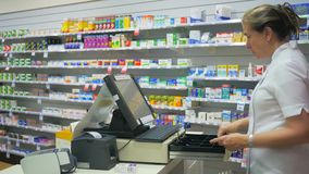Pharmacist processes a transaction at a cash register in a pharmacy. A pharmacist processes a transaction at a cash register in an australian pharmacy stock video footage