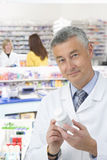 Pharmacist reading label on medicine bottle in pharmacy Royalty Free Stock Photo