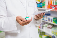 Pharmacist reading prescription and holding medicine Stock Images