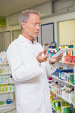 Pharmacist reading prescription and holding medicine Royalty Free Stock Image