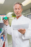 Pharmacist reading prescription and holding medicine Stock Photo
