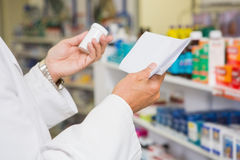 Pharmacist reading prescription and holding medicine Royalty Free Stock Images