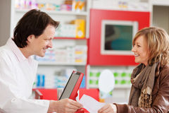 Pharmacist Receiving Prescription Paper From Customer Stock Photography