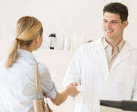 Pharmacist Receiving Prescription Paper From Customer At Store Royalty Free Stock Images